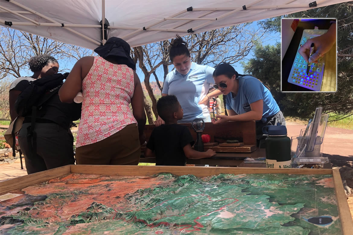 Split image: Volunteers educating the public using the Watershed Terrain model and a water sampling tray in the inset
